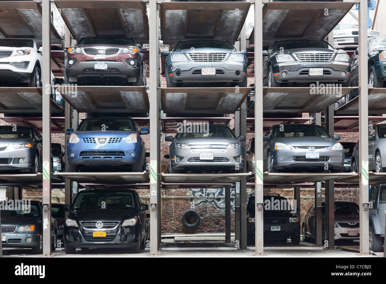 Cars parked in vertical hydraulic parking spaces in a parking lot in New York City. - Stock Image