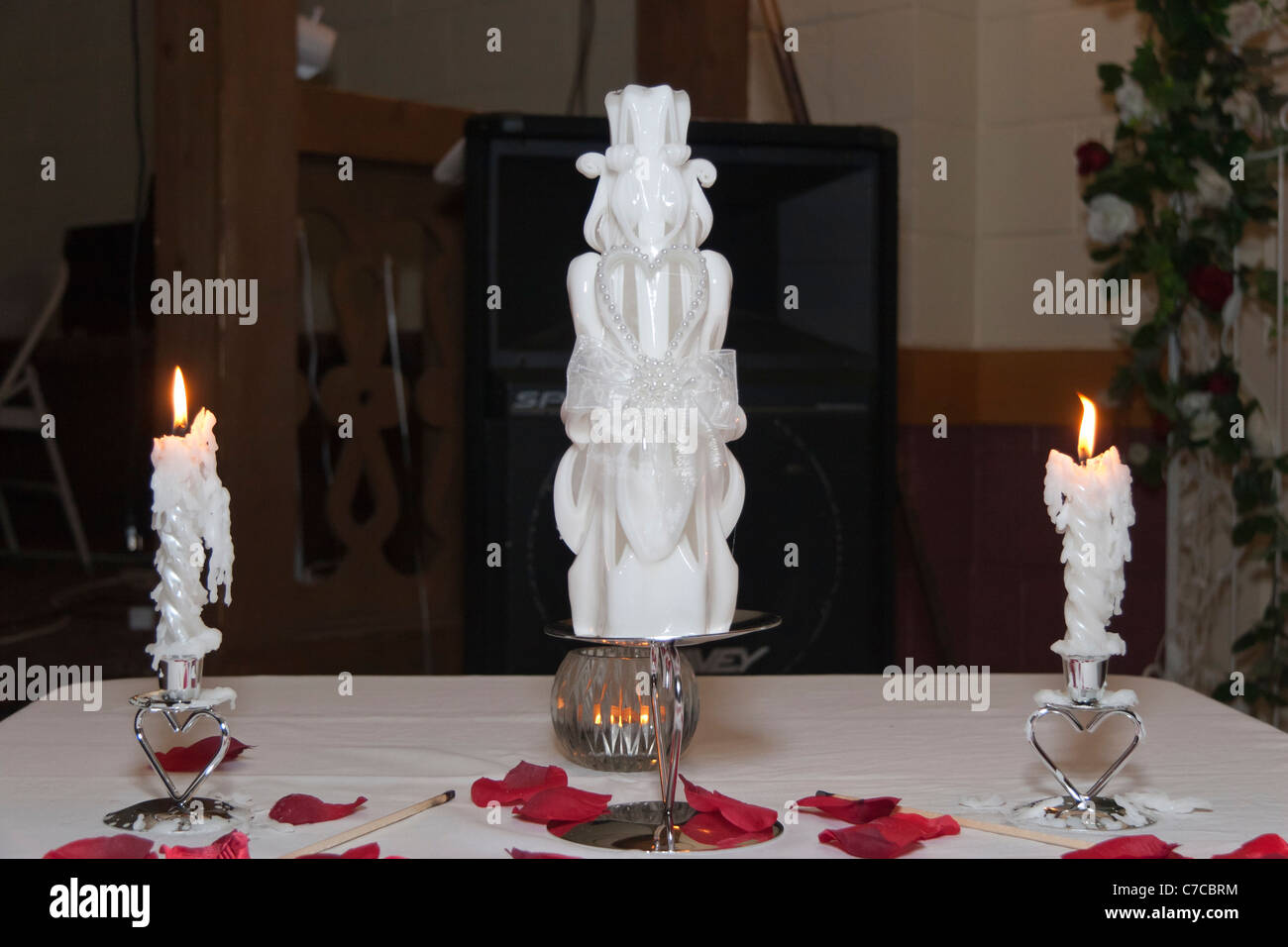 Wedding Unity Candles Lit Up On A Table Decorated With White Cloth And Red  Roses Petals