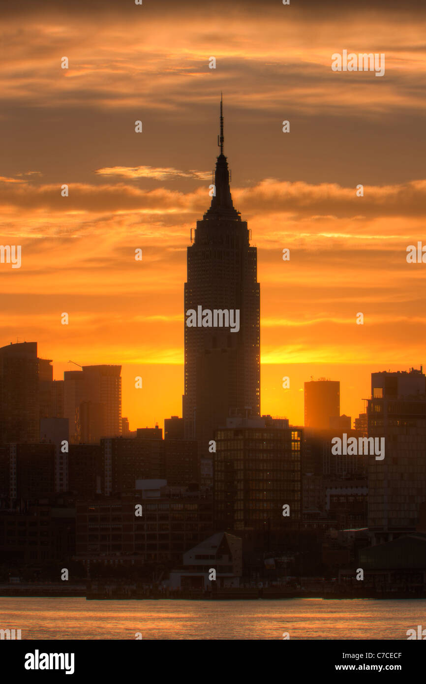 The rising sun shines from behind the Empire State Building just after sunrise in New York City. - Stock Image