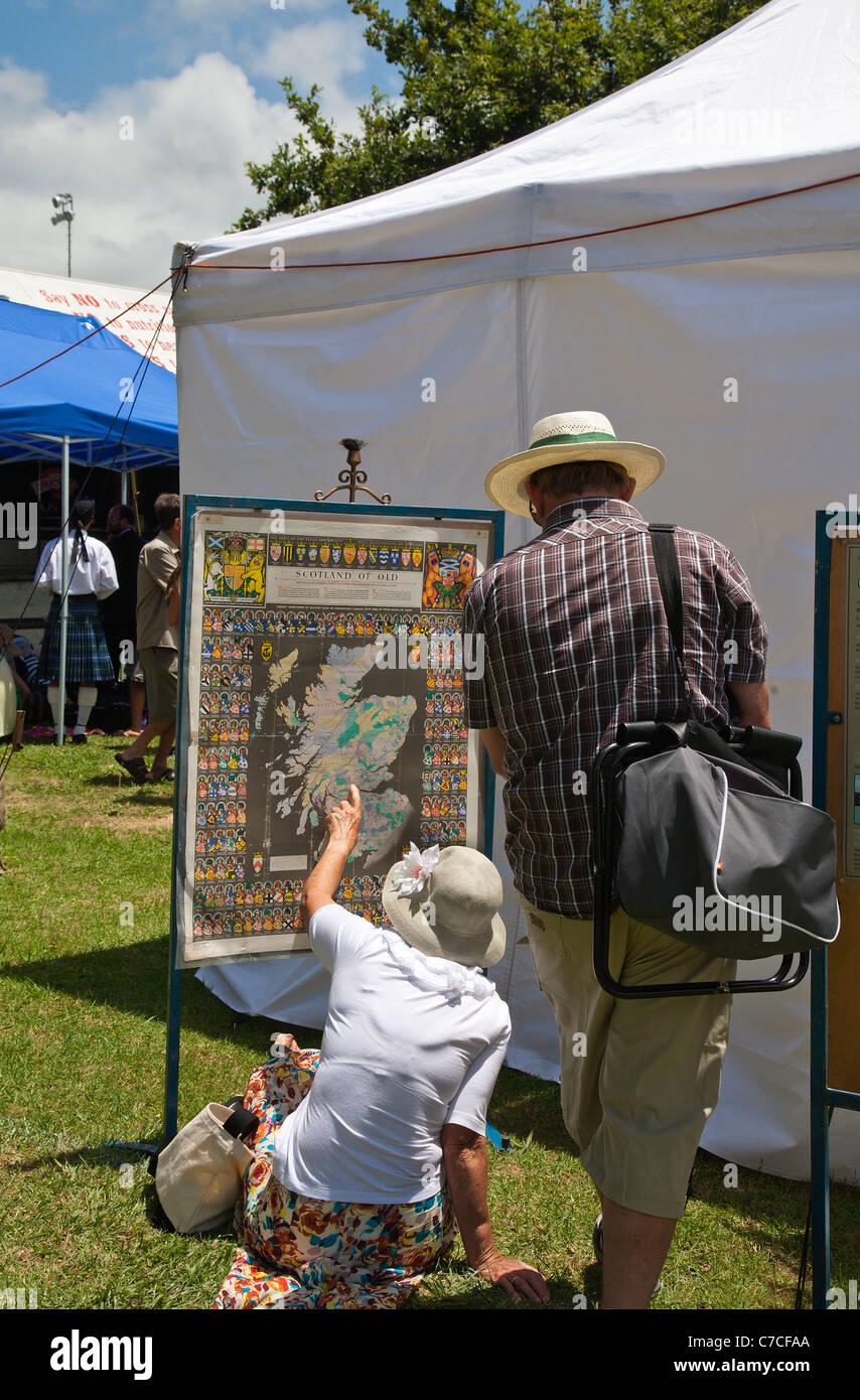 Two people looking at an old ancestral map of Scotland at the Waipu Highland Games.. Northland, North Island, New - Stock Image