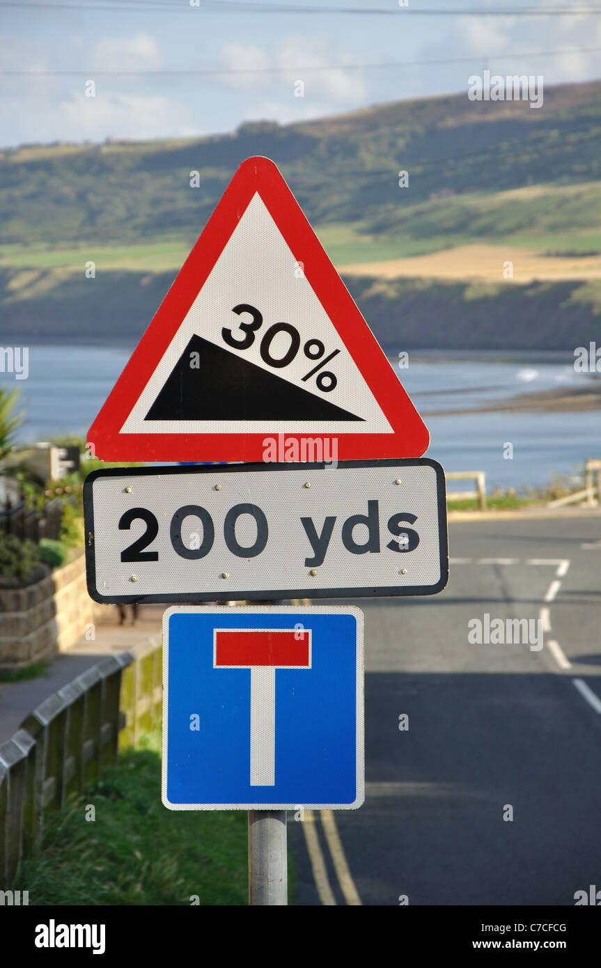 road sign warning of 30 percent downward gradient on approach to steep hill, Robin Hoods Bay, North Yorkshire, England, - Stock Image