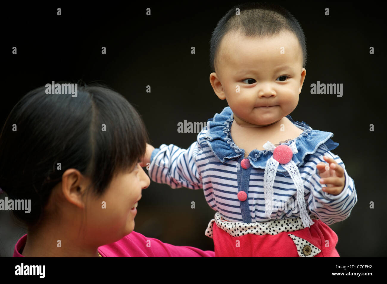 A migrant mother from rural Hennan province with her child in Beijing, China.16-Sep-2011 - Stock Image