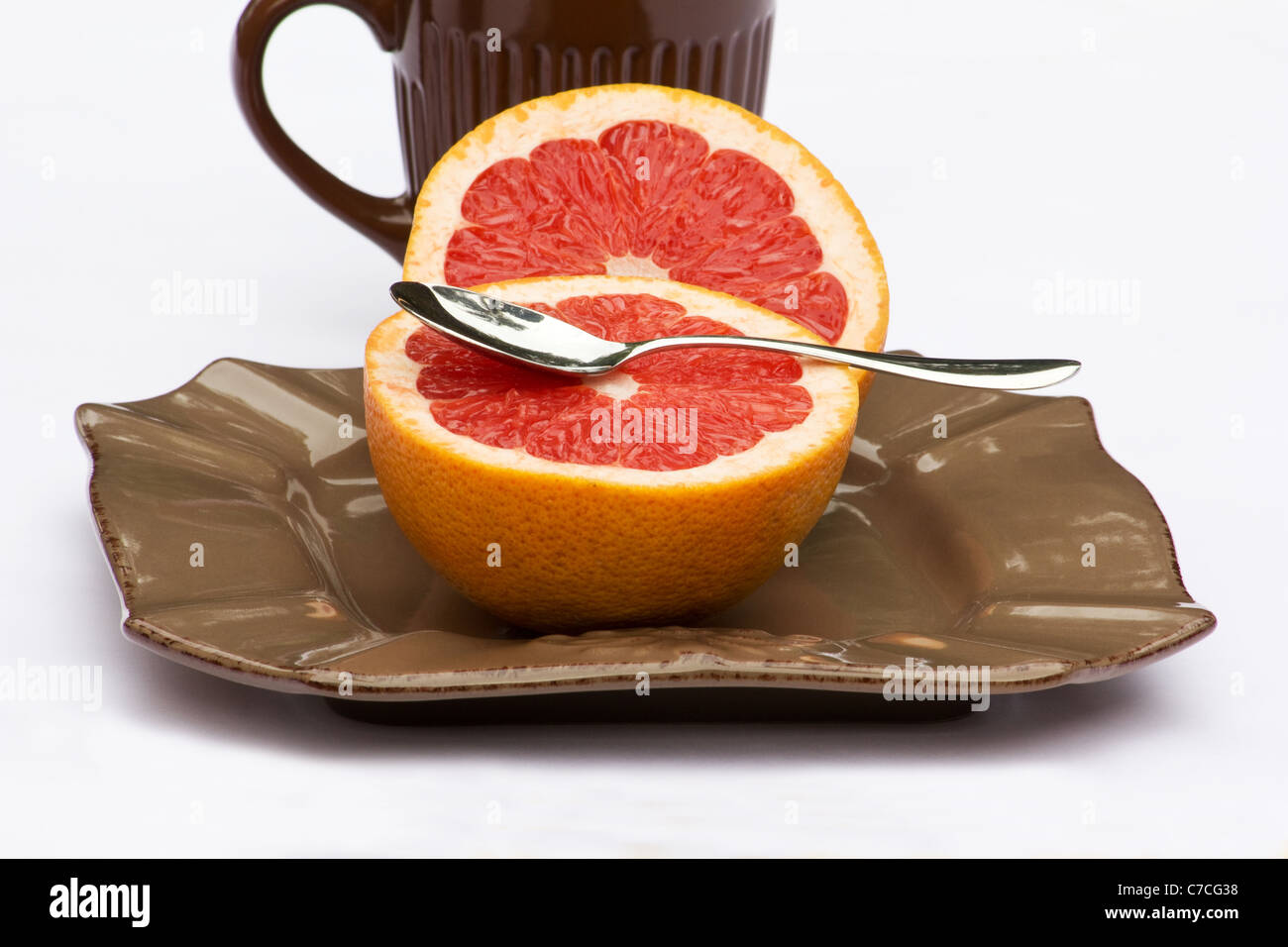 Fresh ruby grapefruit cut in halves on white background - Stock Image