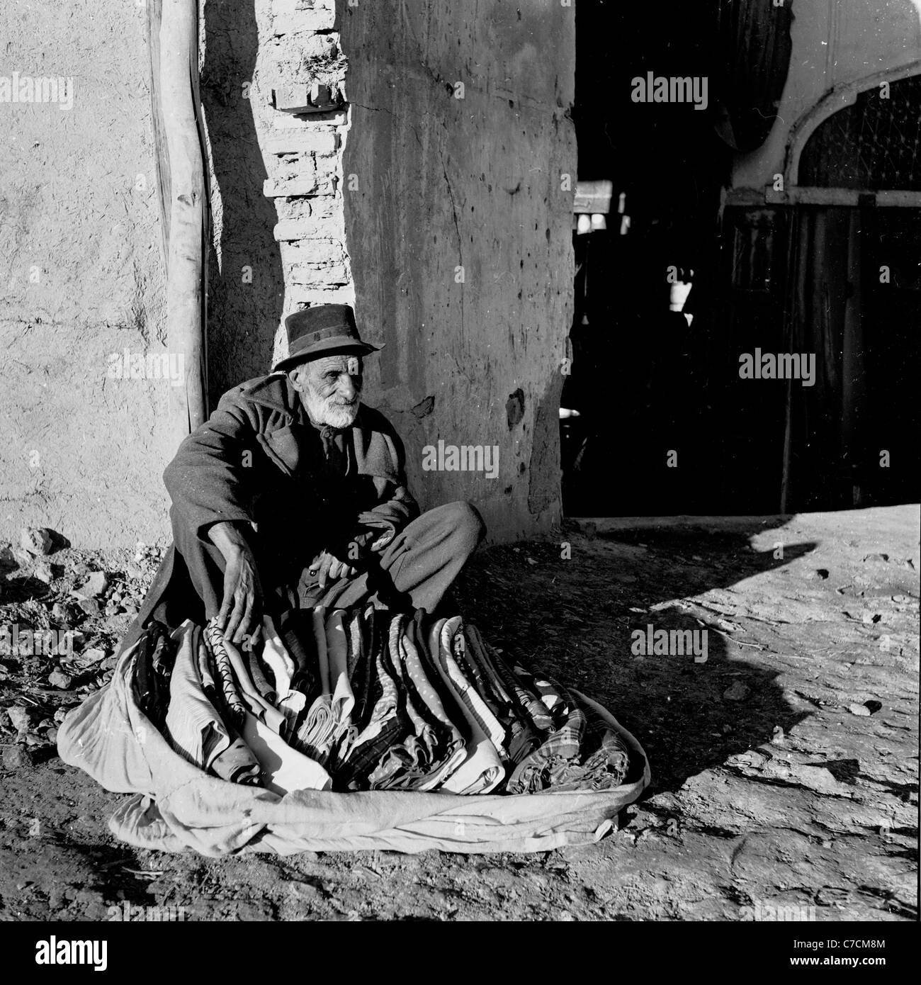 1950s. Historical picture showing bearded old man with hat sitting beside old building, selling blankets, Isfahan, - Stock Image