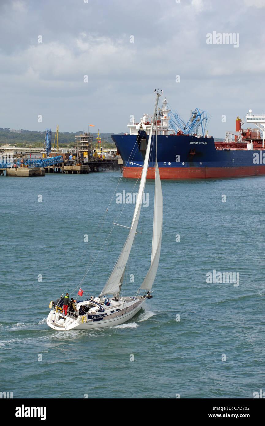 Sailing on Southampton Water UKSA Freedom passing the bulk tanker Navion Oceania berthed at Fawley Marine Terminal - Stock Image