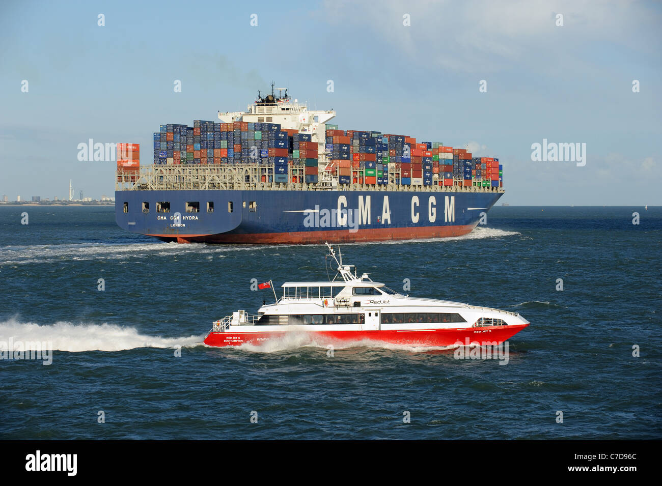 Fastcat passenger ferry crossing The Solent southern England UK Passing the CMA CGM Hydra a container carrier outbound - Stock Image