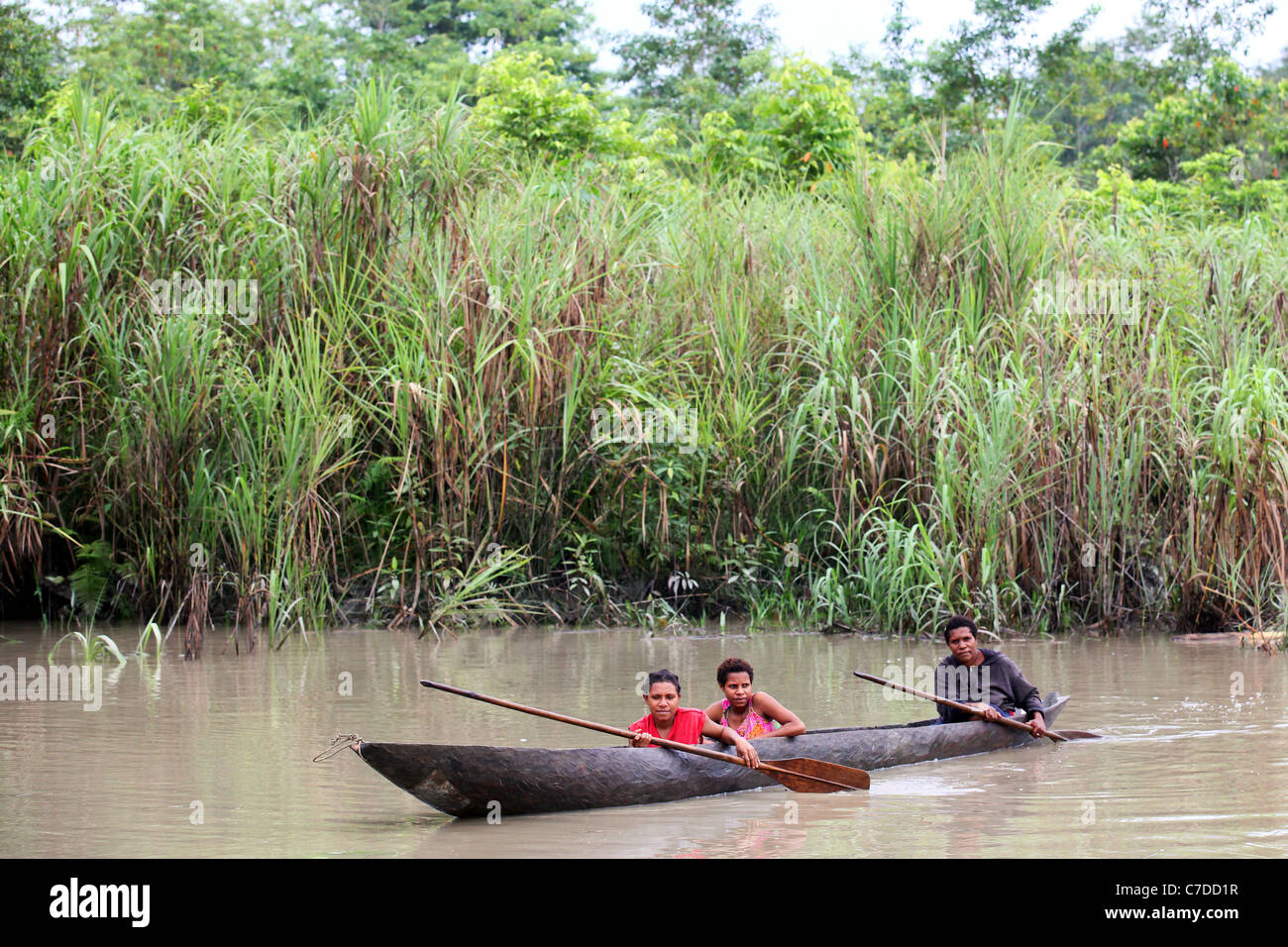 Three girls in a dugout canoe on a river in Papua New Guinea - Stock Image