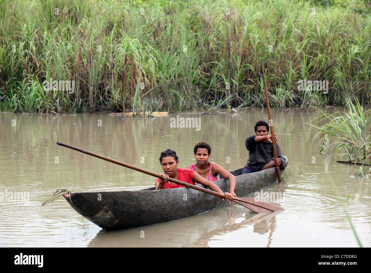 Three girls in a dugout canoe on a river in Papua New Guinea Stock Photo
