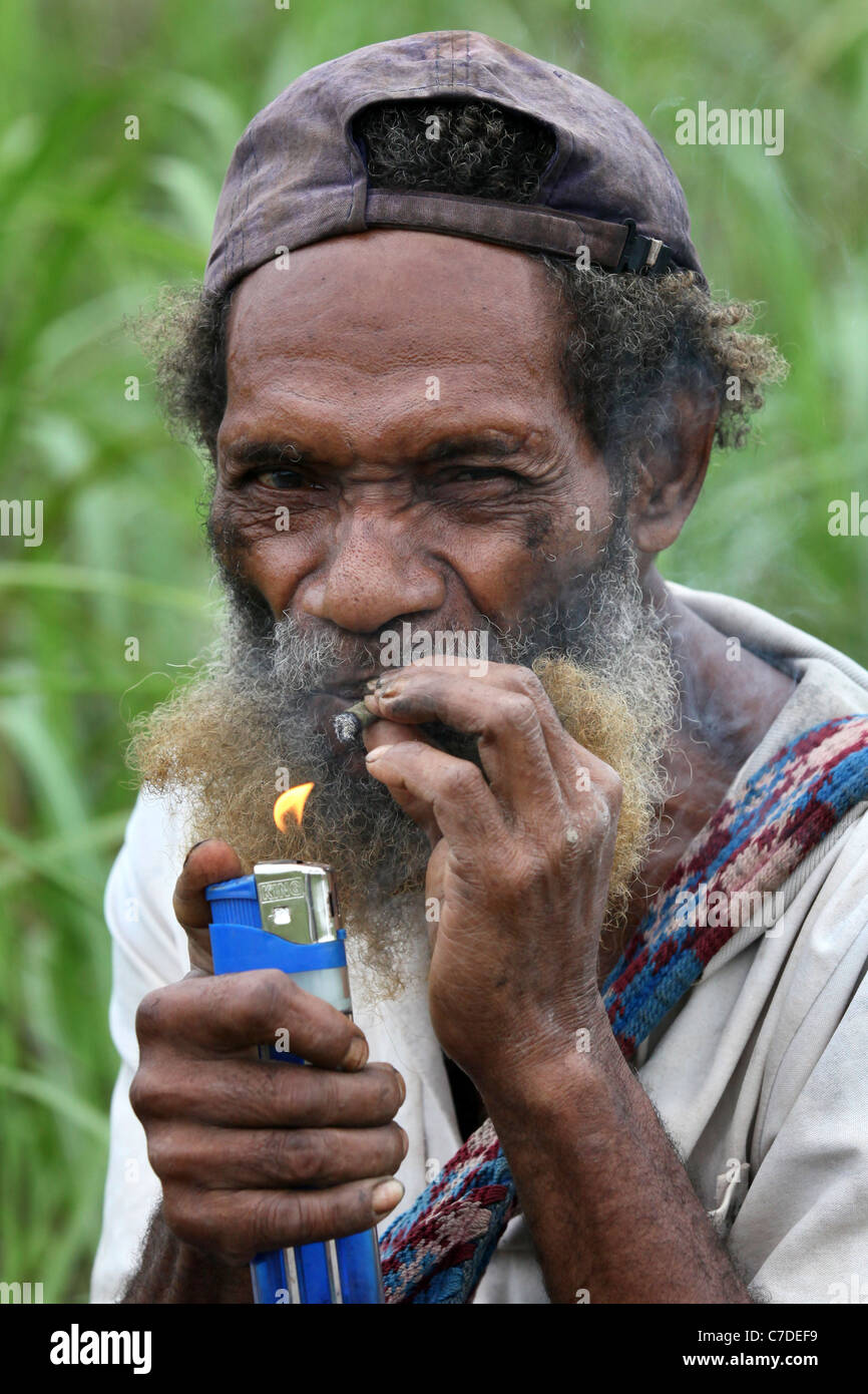 old man lightening a cigarette with a big lighter, Papua New Guinea - Stock Image