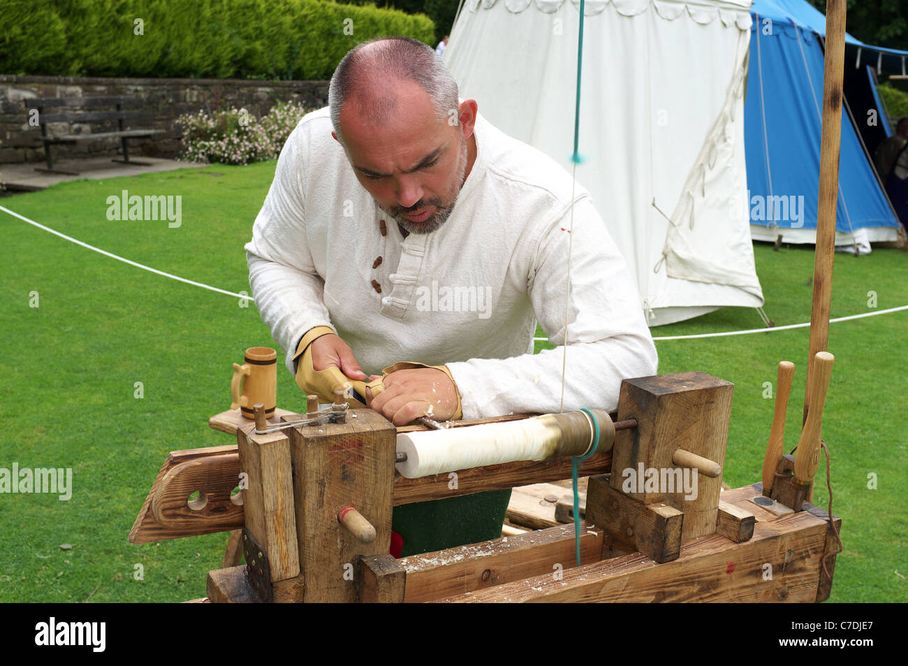 Man demonstrating the traditional method of carving wood using a foot operated lathe, Kilmarnock, Ayrshire, Scotland, - Stock Image