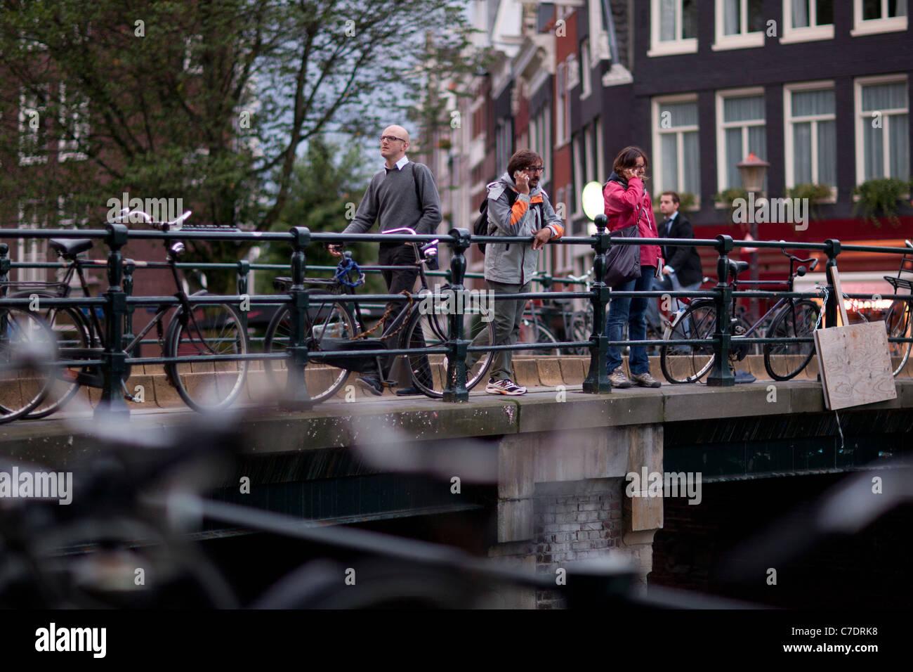 People crossing a bridge in Amsterdam Stock Photo