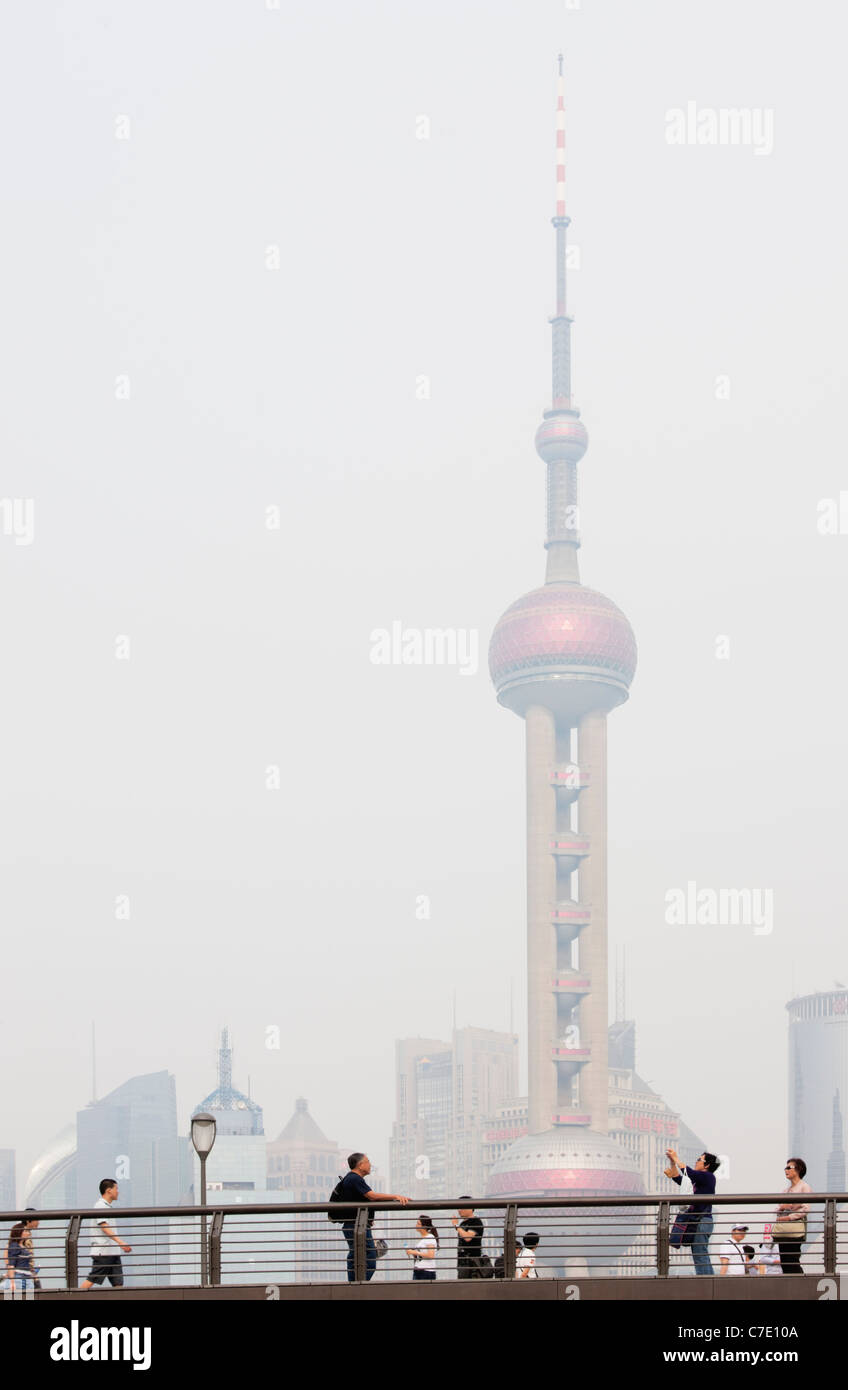 Sightseers on The Bund, Oriental pearl Tower in background, Pudong, Shanghai, China - Stock Image