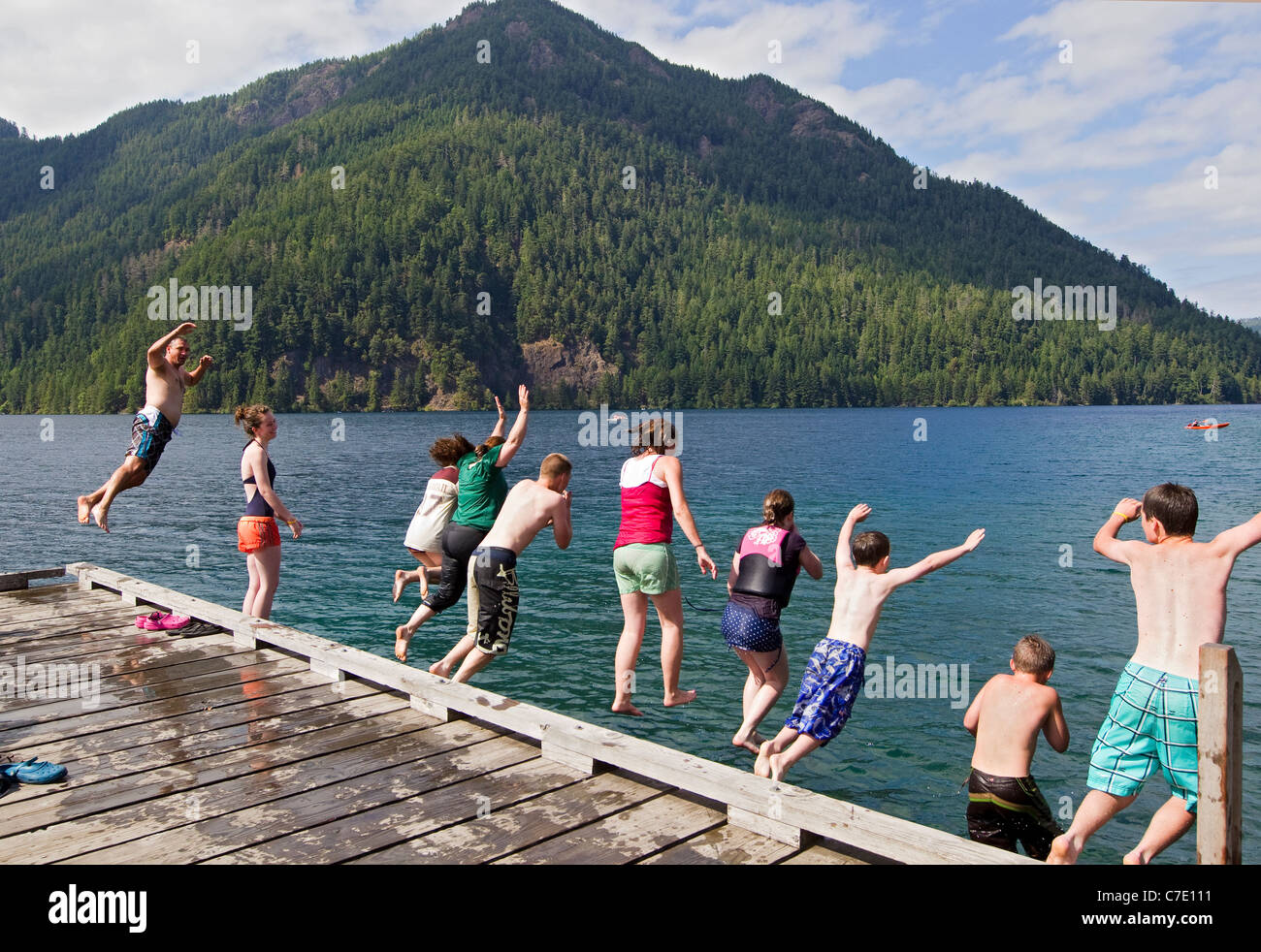 Family leaps into lake from dock, summertime lake fun - Stock Image