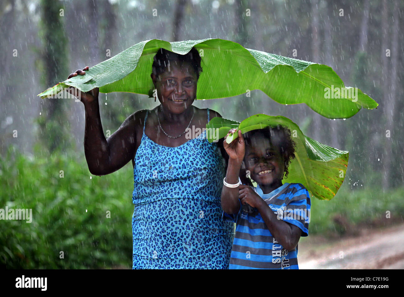Mother and child using banana leaf as umbrella against pouring rain. Jungle of Bougainville Island, Papua New Guinea - Stock Image