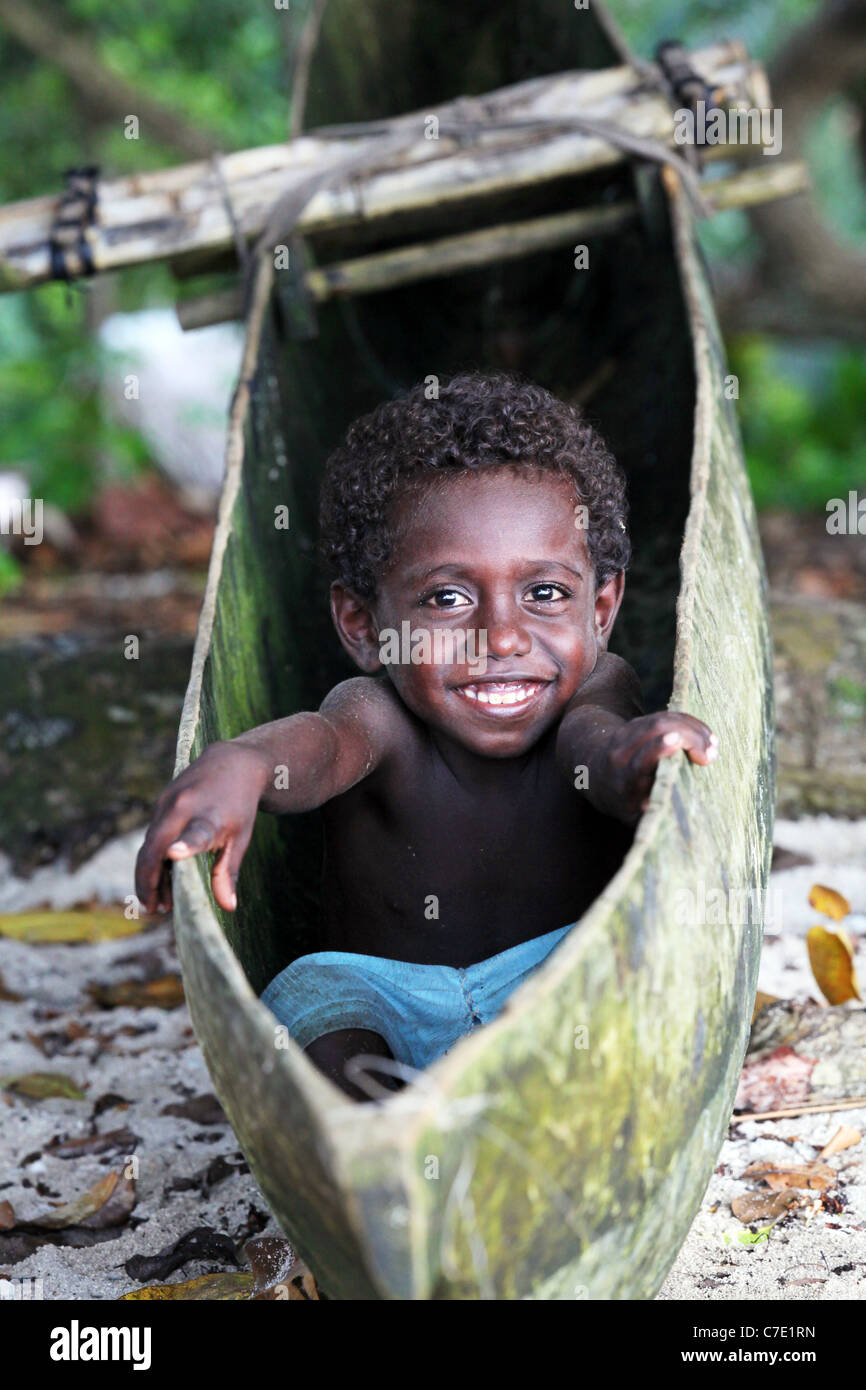Boy sits in a dugout canoe, Bougainville Island, Papua New Guinea - Stock Image