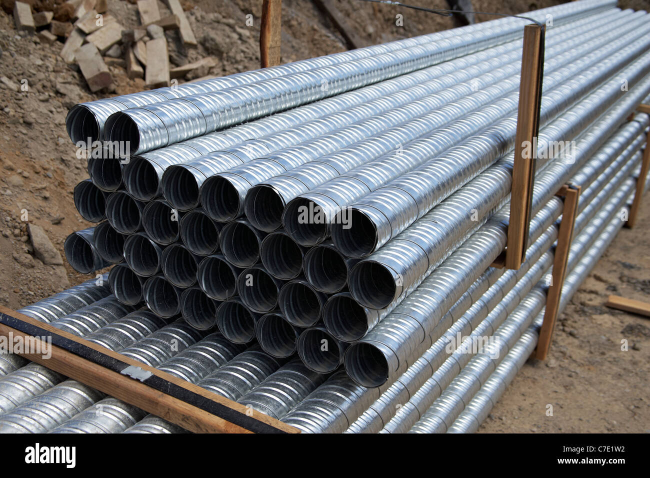 Stack of galvanized pipes at construction site - Stock Image