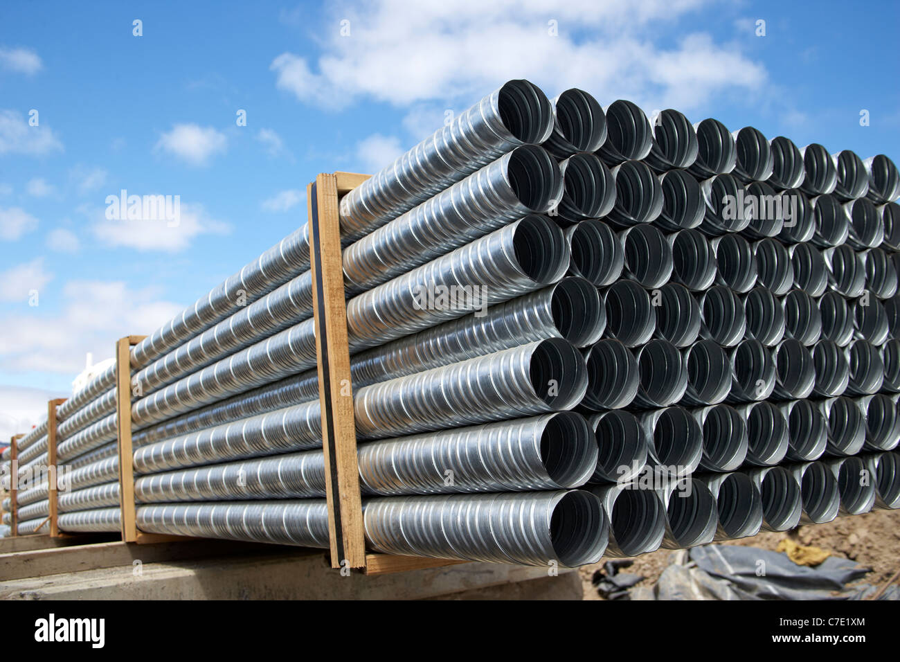Galvanized steel pipes stacked at construction site - Stock Image
