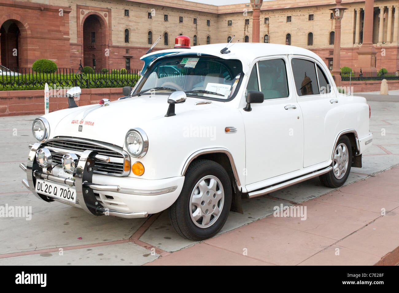An iconic Hindustan Ambassador car parked outside of the Indian Government Building in New Delhi, India - Stock Image