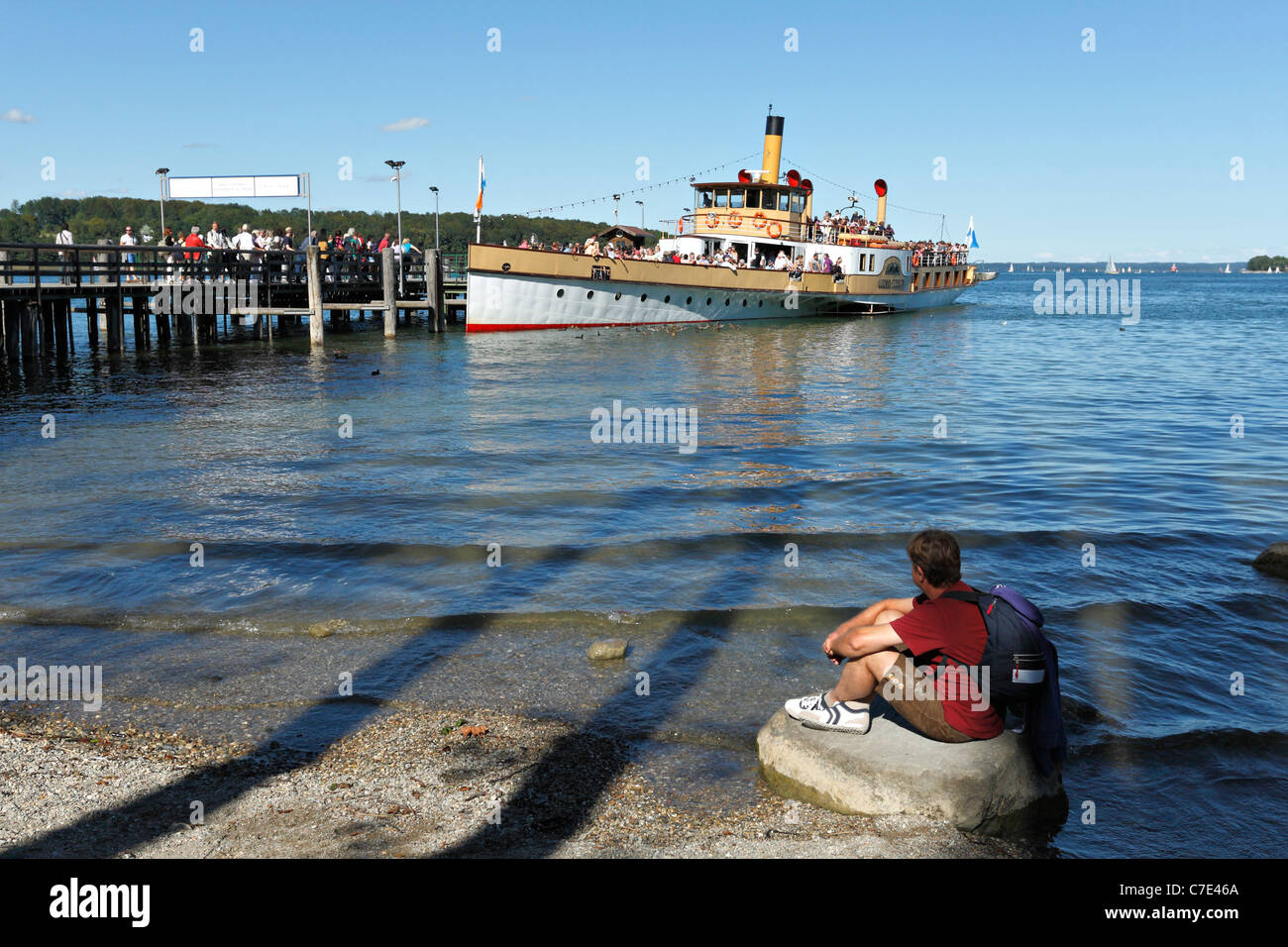 Man sitting on foreshore watching a Chiemsee Ferry Boat at the Herreninsel, Chiemgau Upper Bavaria Germany Stock Photo