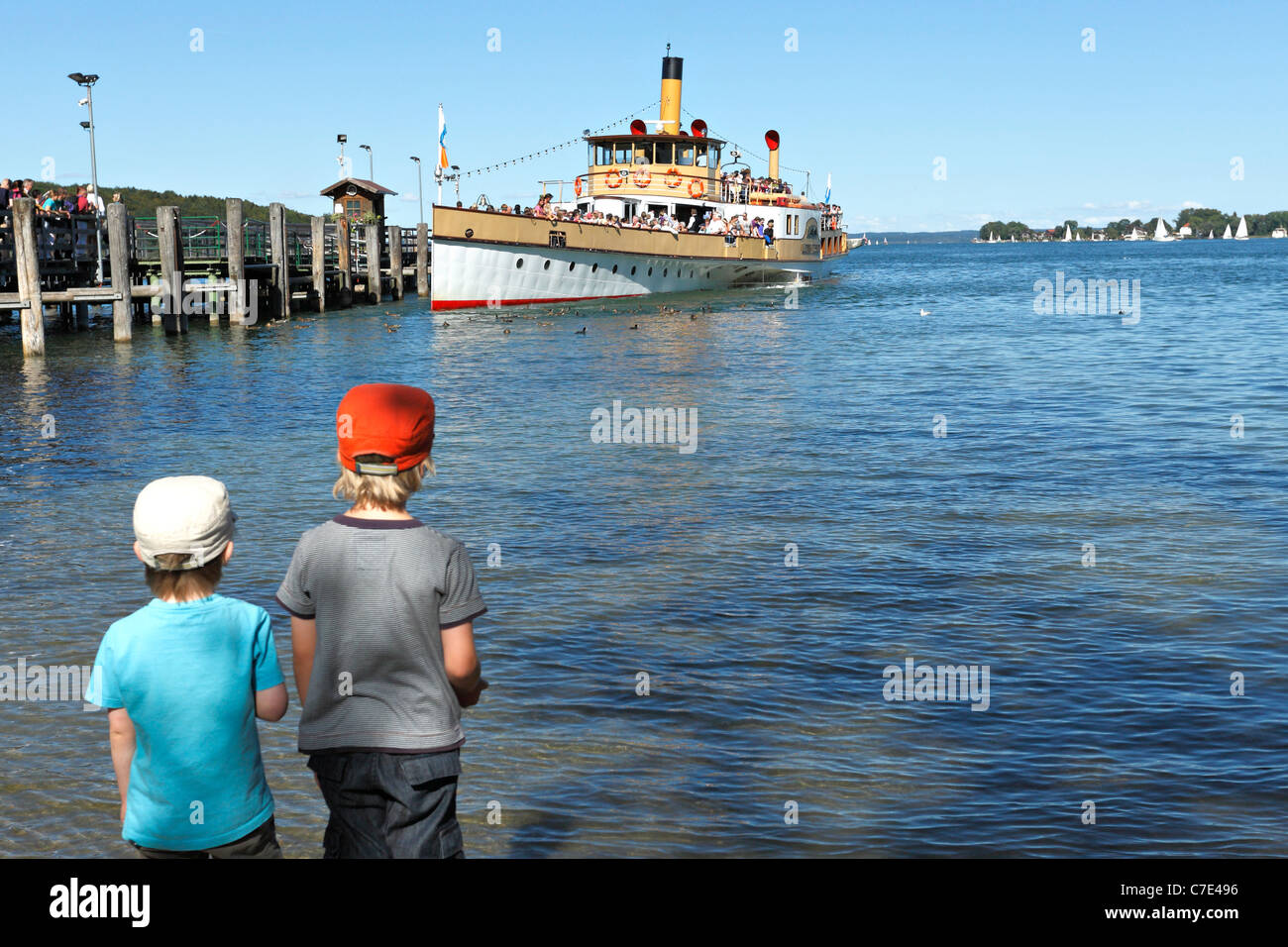 Children on foreshore watching a Chiemsee Ferry Boat at the Herreninsel, Chiemgau Upper Bavaria Germany - Stock Image