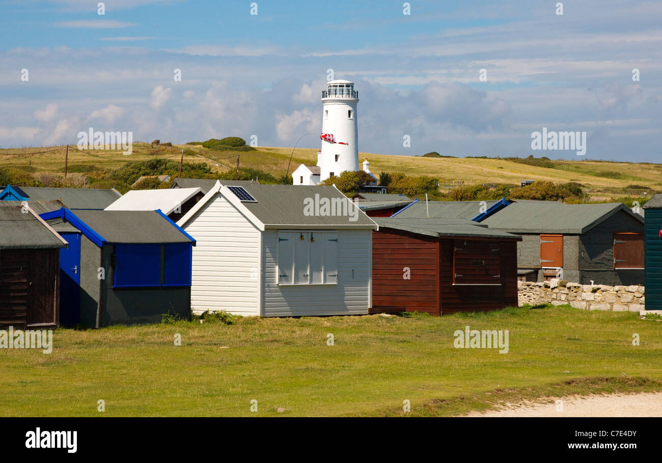 Holiday chalets fronting the coast at Portland Bill in Dorset with the old lighthouse inland - Stock Image