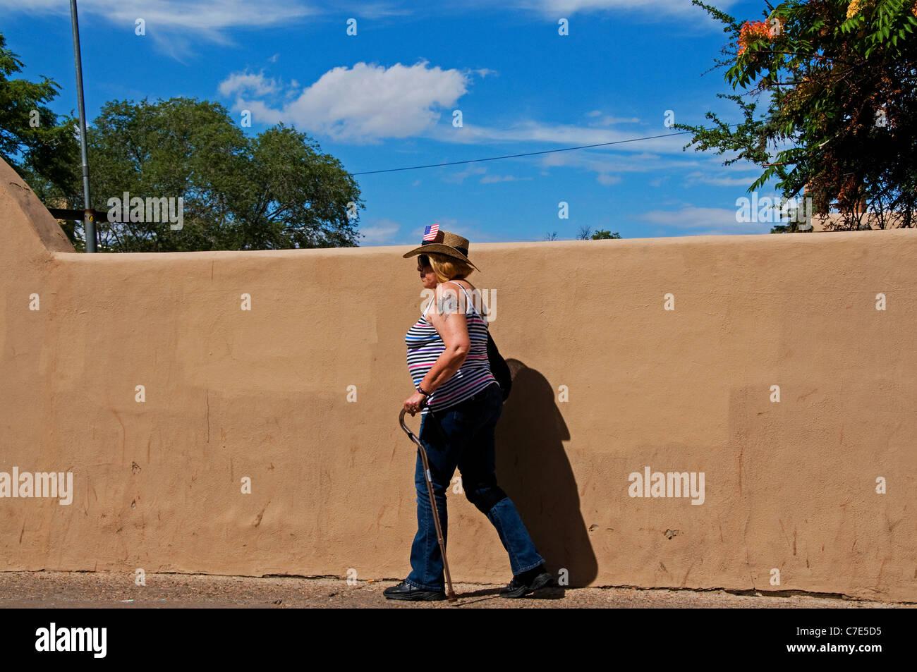 mature woman walking street photojournalism - Stock Image