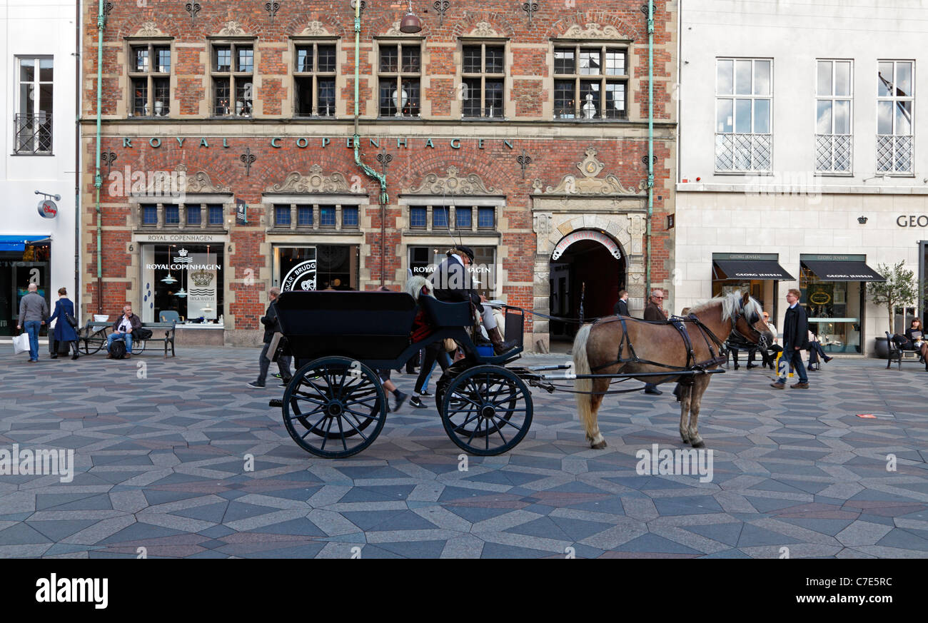 Horse-drawn cab in front of the Royal Copenhagen porcelain shop  on the main pedestrian and shopping street Strøget, - Stock Image