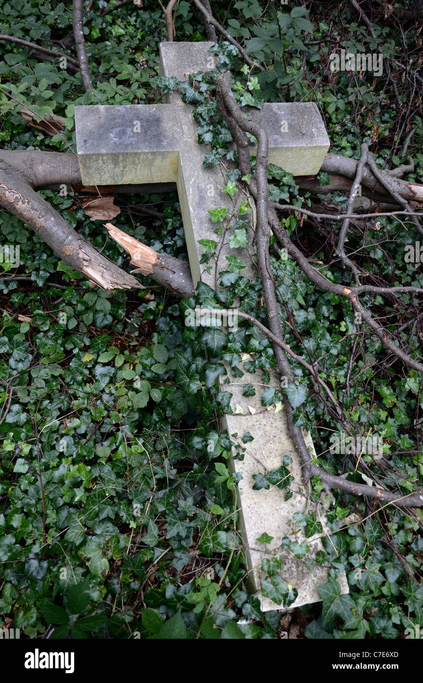 A broken cross overgrown with ivy and fallen branches in Warriston Cemetery, Edinburgh, Scotland, UK. - Stock Image