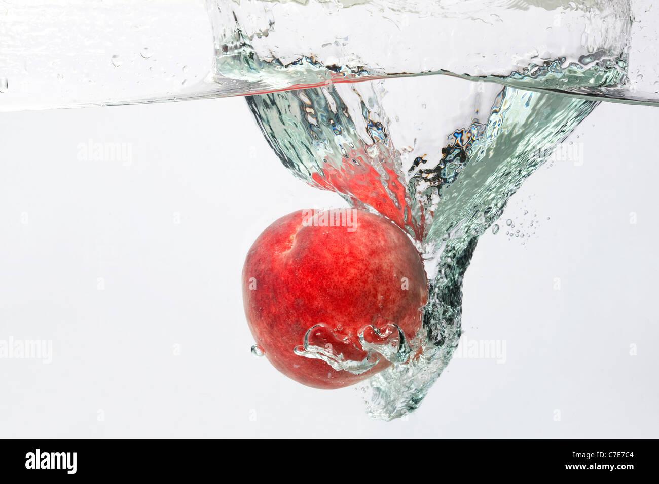Peach Splashing in Water - Stock Image