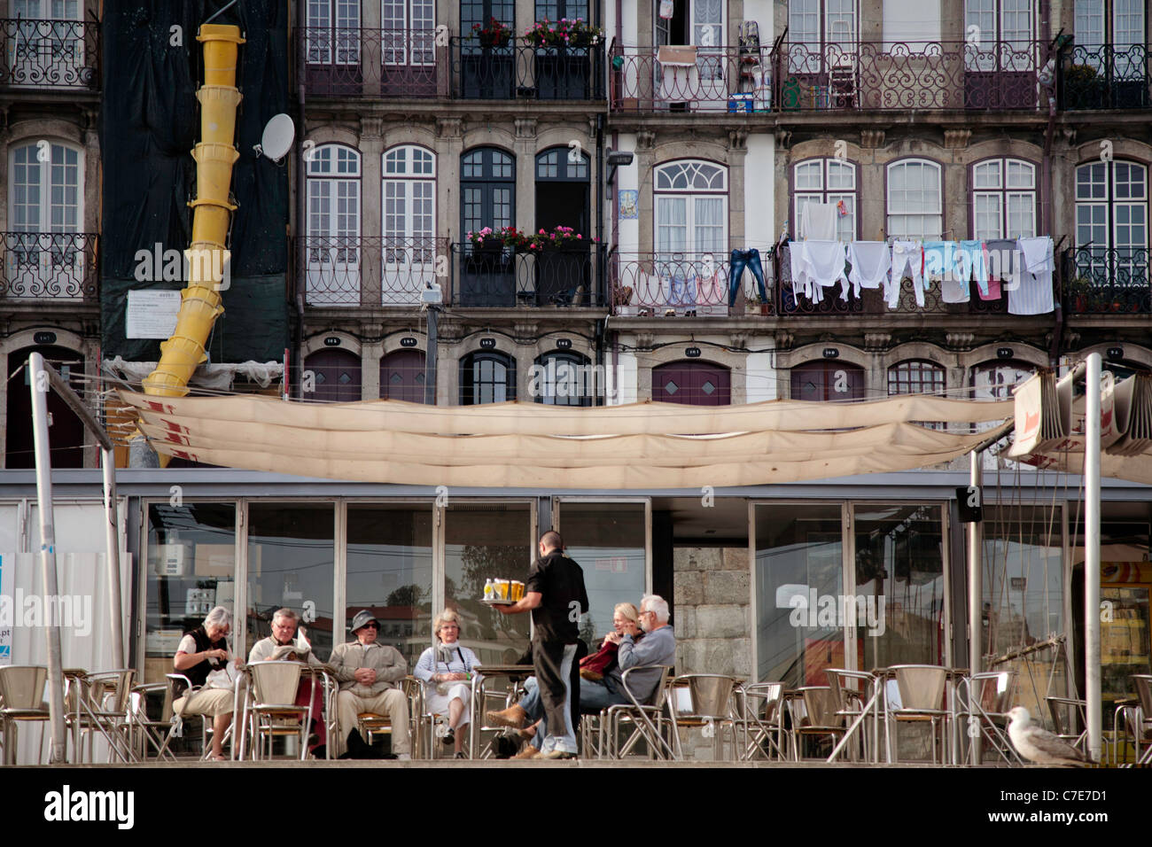 Visitors having a drink at a quayside restaurant, with traditional buildings, Porto - Stock Image