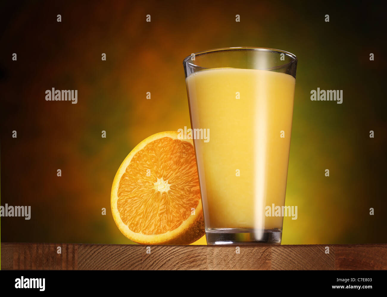 Glass of orange juice on a wooden board. - Stock Image