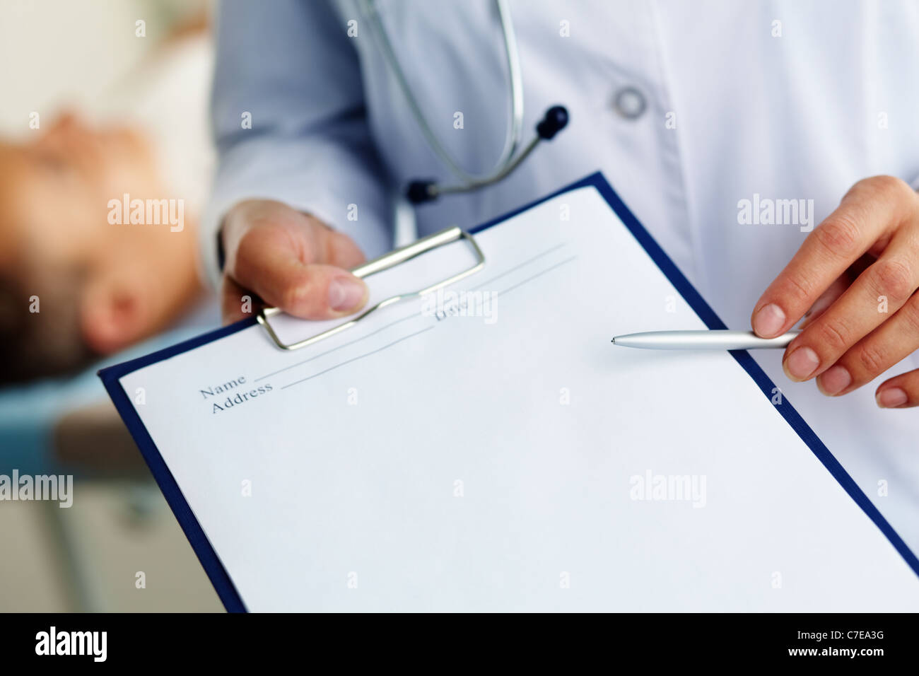 Hand of female doctor with pen pointing at clipboard - Stock Image