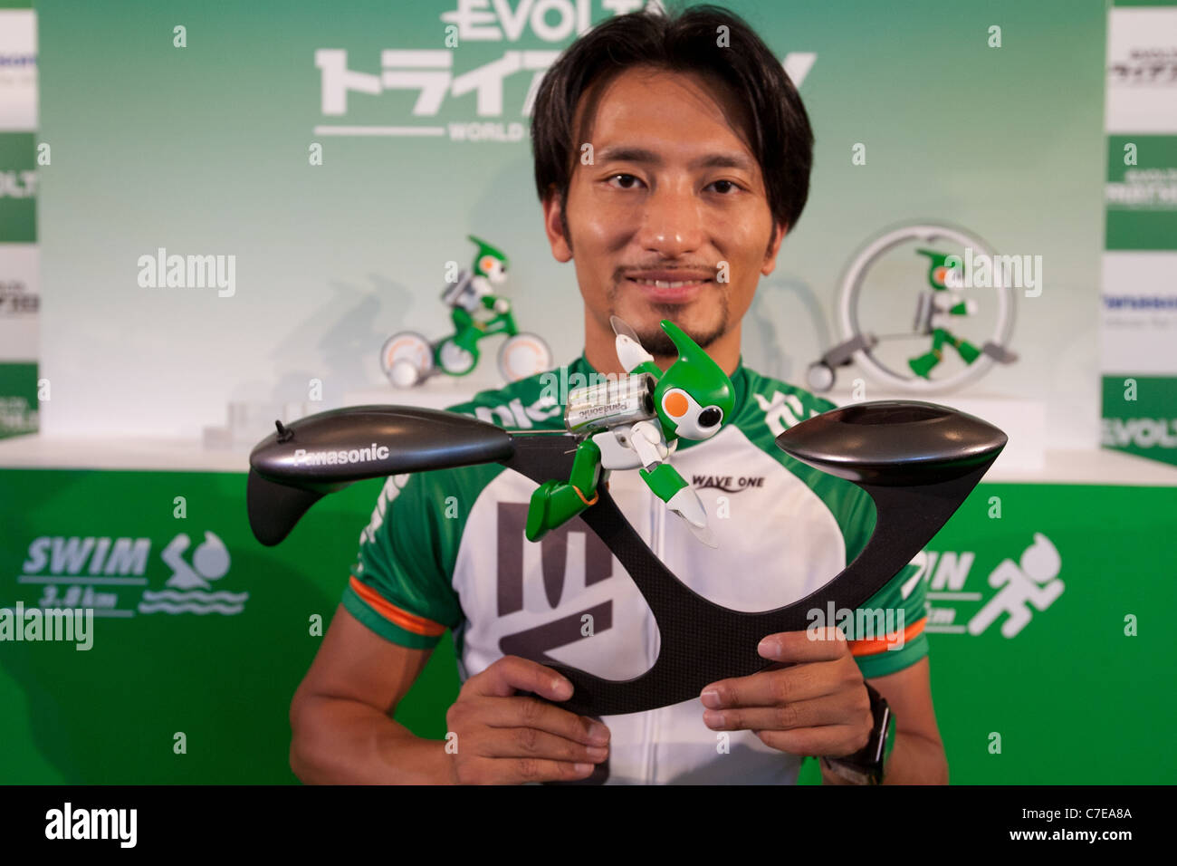Tomotaka Takahashi poses for a photograph as he holds up the new swim robot during the Panasonic EVOLTA Challenge - Stock Image