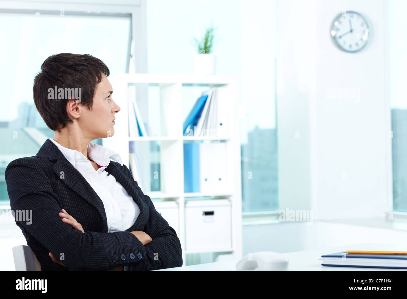 photo of smart businesswoman sitting in office and looking at clock