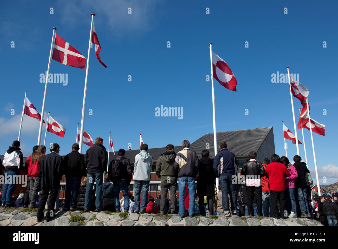 Danish and Greenland flags above people waiting to glimpse the Danish Royal Family, National Day, celebrating Self - Stock Image
