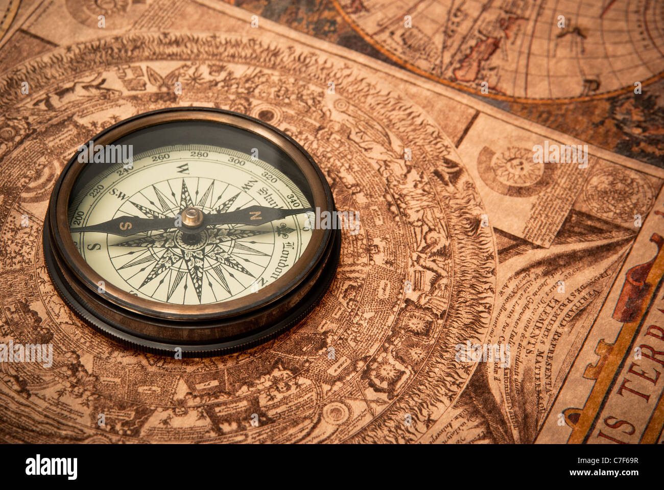 antique compass lying on old style map sepia toned stock image