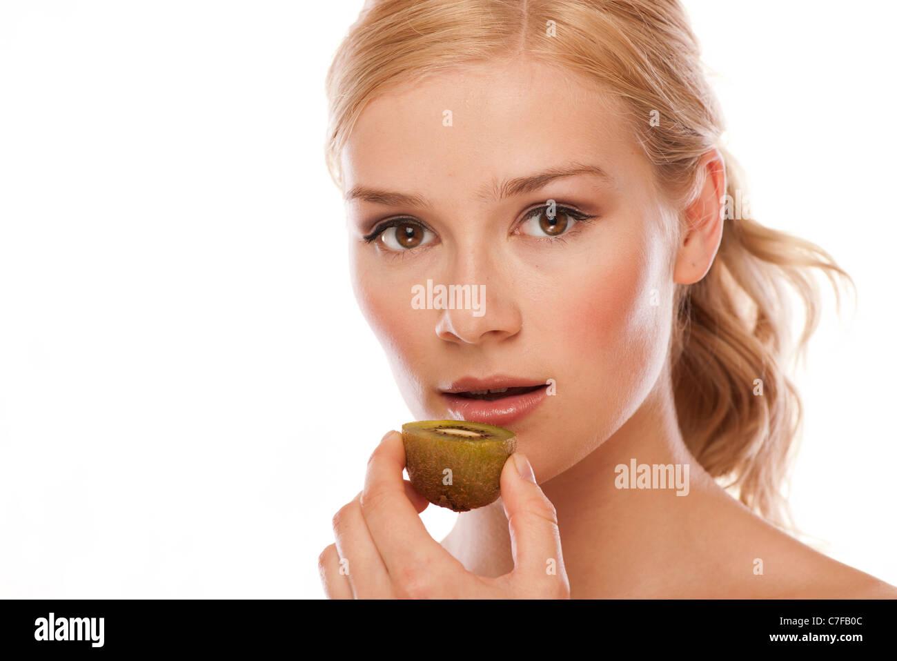 woman eating a kiwi fruit - Stock Image