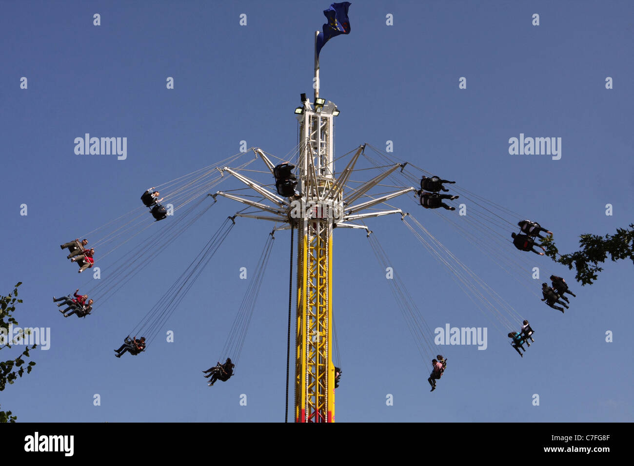 people whirling around on a funfair ride called the star flyer on the embankment of the River Thames - Stock Image