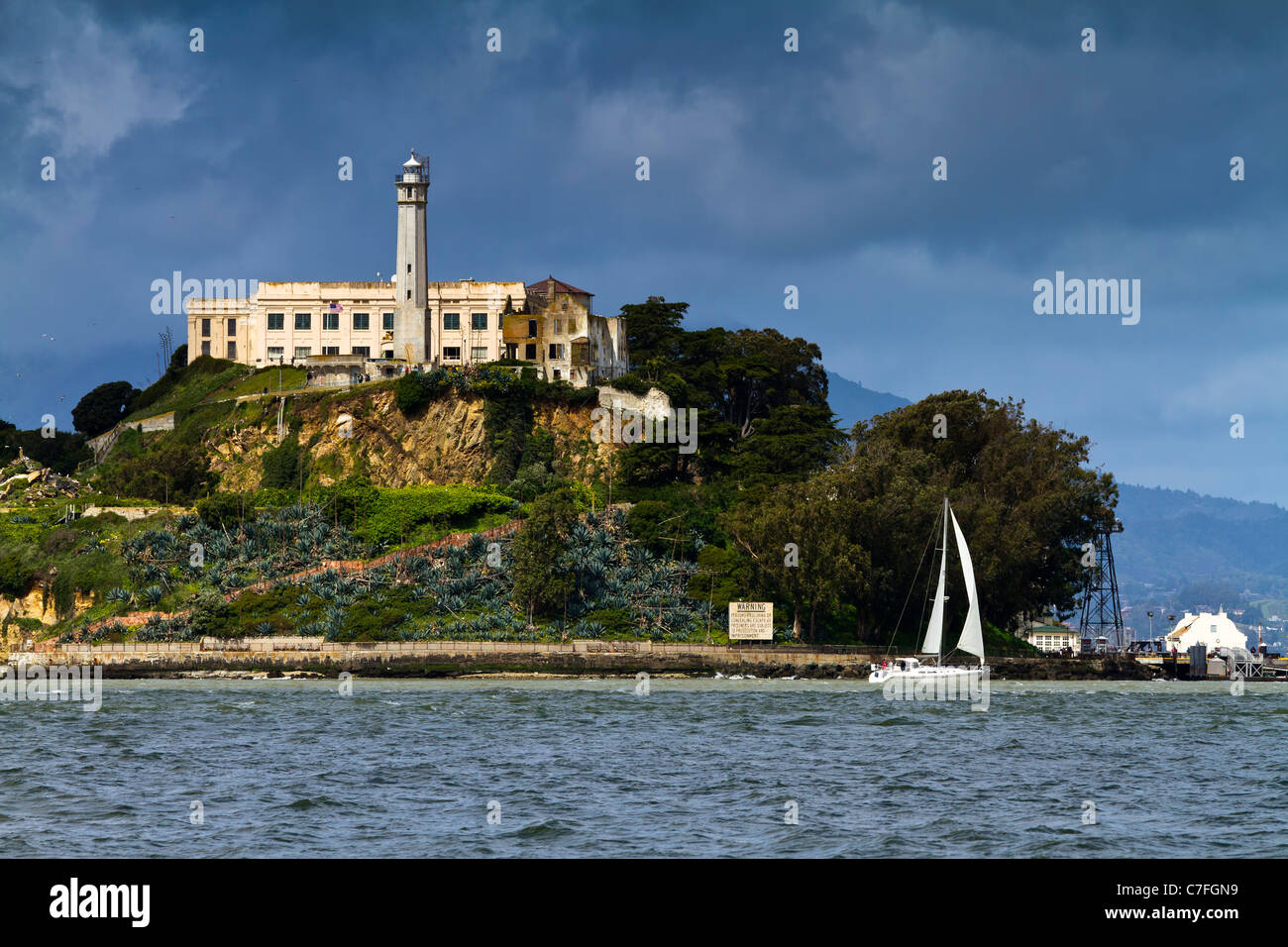 Alcatraz island dramatically spotlit by a break in the clouds as a sailboat passes near its shore. - Stock Image