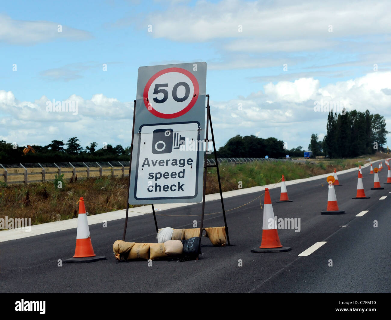 A motorway sign that warns of a speed camera and an average speed check of 50mph - Stock Image