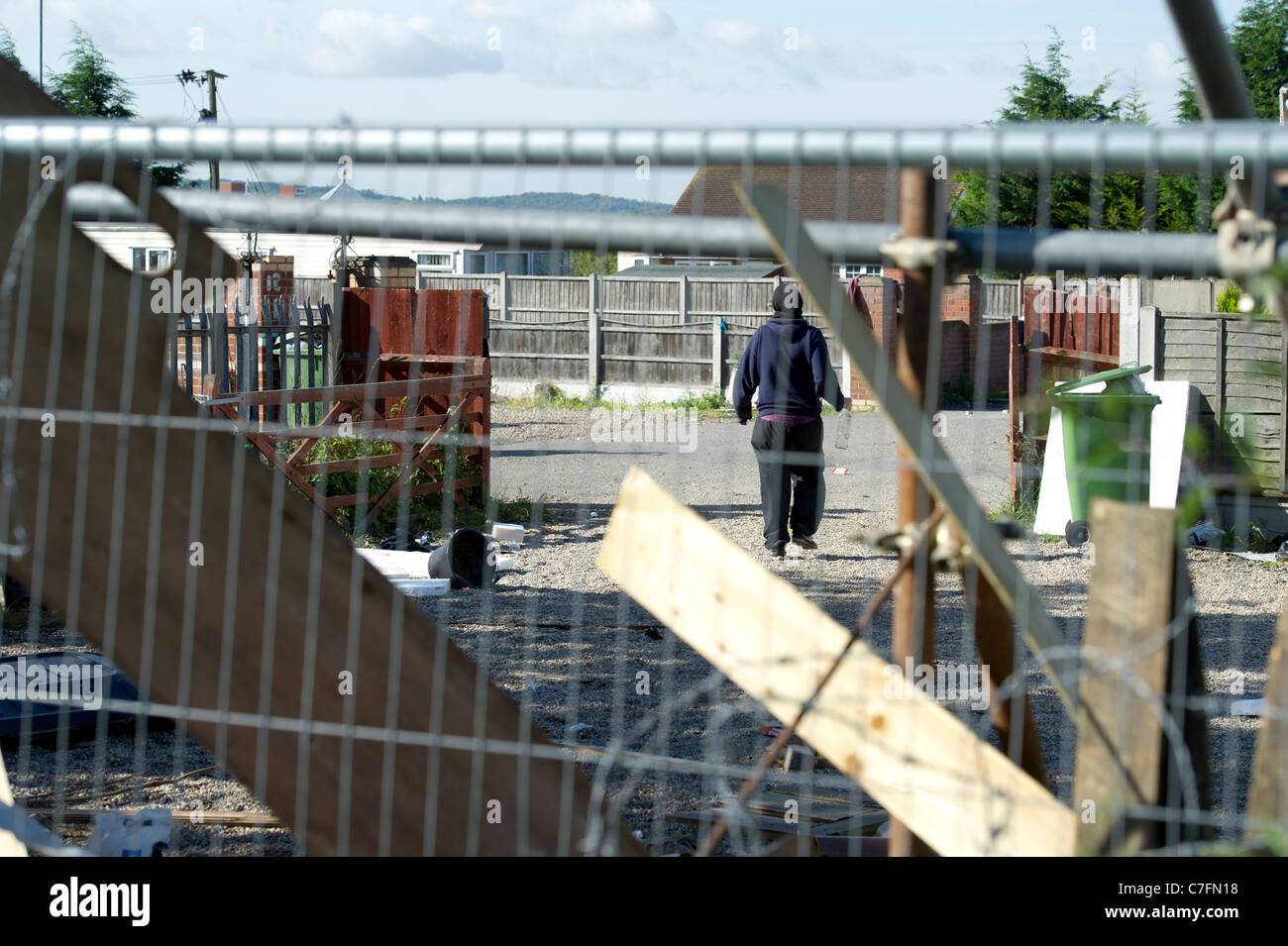 Dale Farm eviction. Protester walking around the illegal traveller site seen through the fencing erected to keep - Stock Image