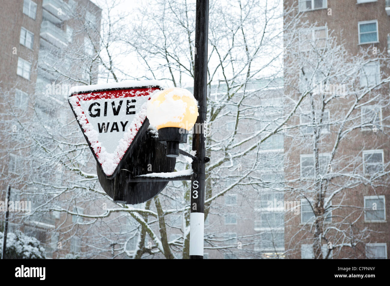 Give Way road sign covered in snow, London December 2011, England, UK Stock Photo
