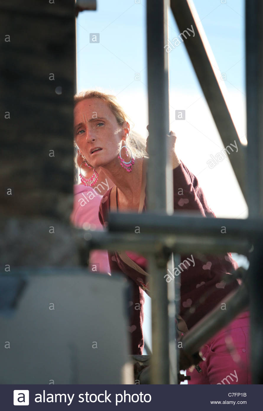 A traveller woman looks out from behind the barricade at the illegal Dale Farm travellers site in Crays Hill Essex - Stock Image