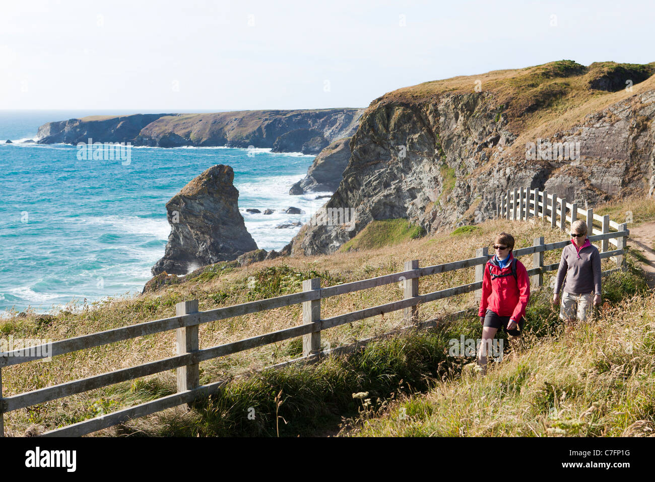 Walkers on the South West Coast Path National Trail at Bedruthan Steps on the west Cornish coast near Bedruthan, - Stock Image