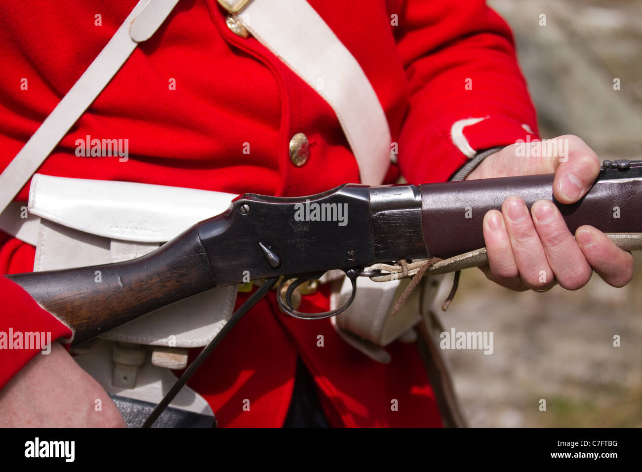 Victorian British army redcoat soldier holding Martini Henry breech loading rifle, UK. The Martini-Henry rifle was - Stock Image