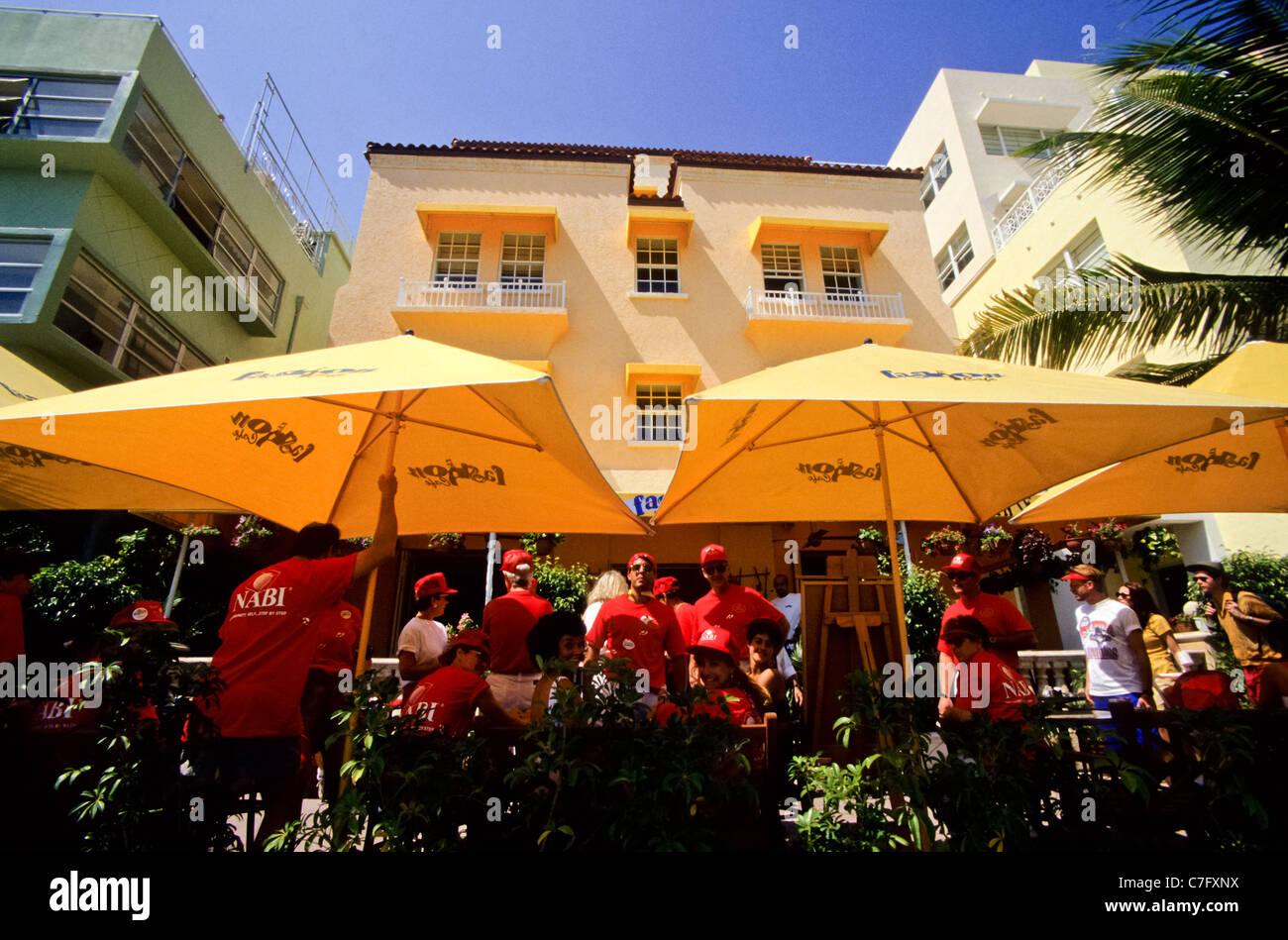 Group of people under umbrellas on Miami beach road or Ocean Boulevard in Florida, USA - Stock Image
