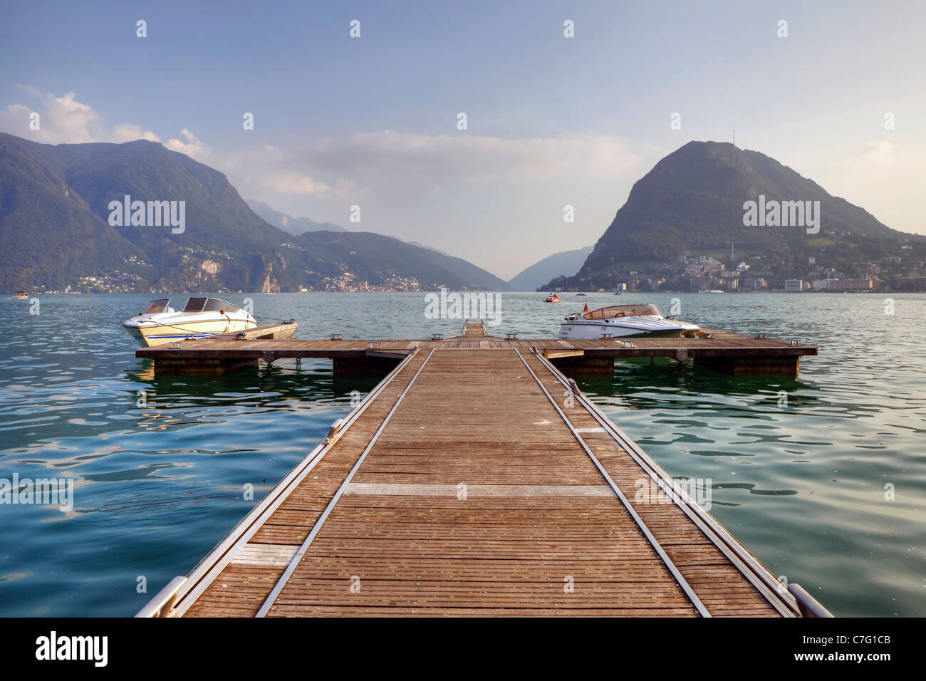 an impressive boat dock on Lake Lugano, with views of Monte Salvatore - Stock Image