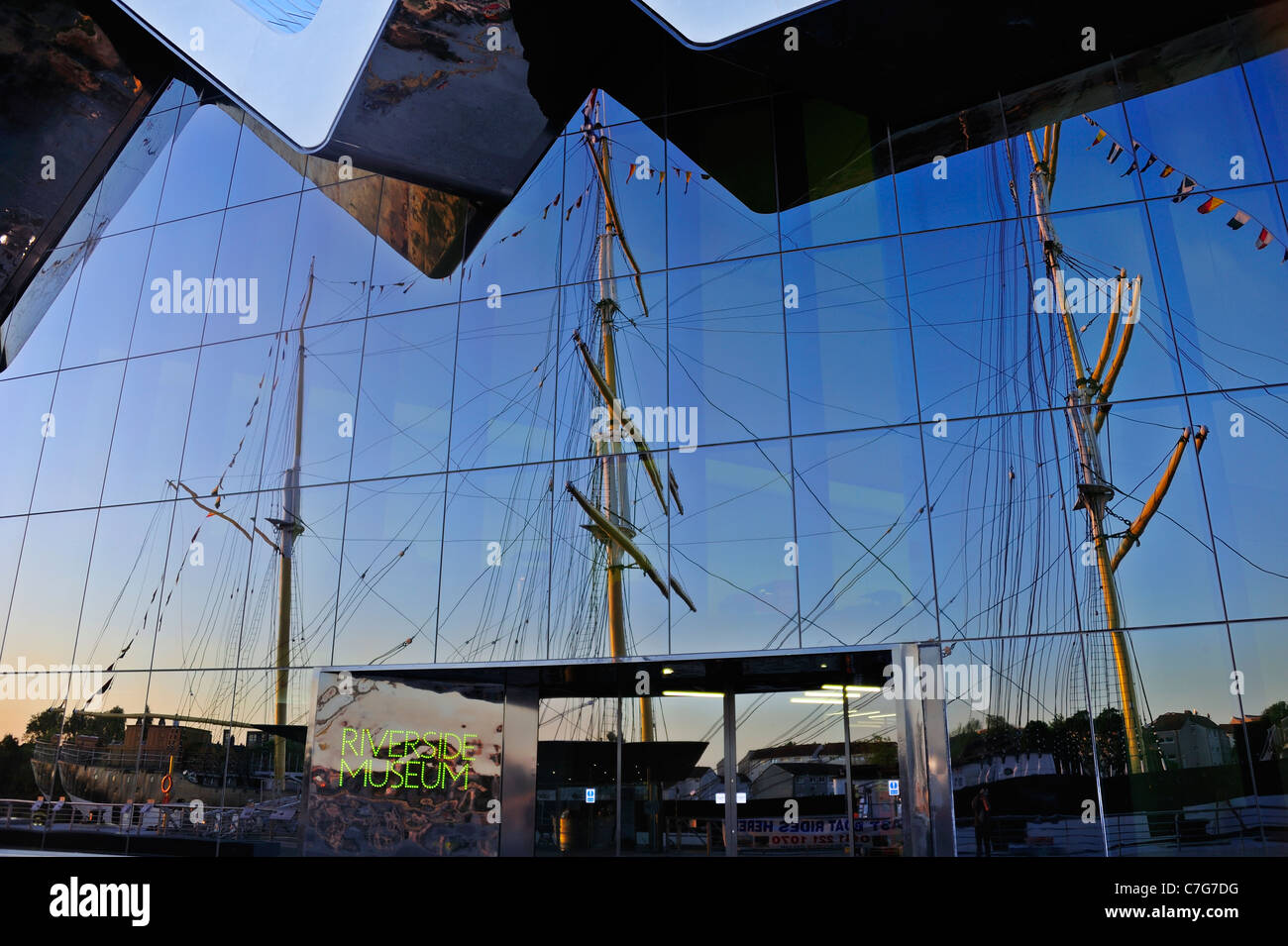 The facade of the Riverside Museum in Glasgow with the three-masted barque, the Glenlee reflected in the glass - Stock Image