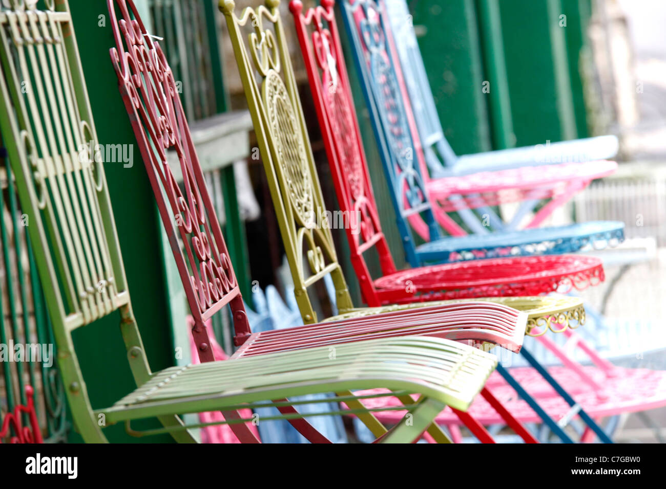 vintage iron chairs on display in a shop front - Stock Image
