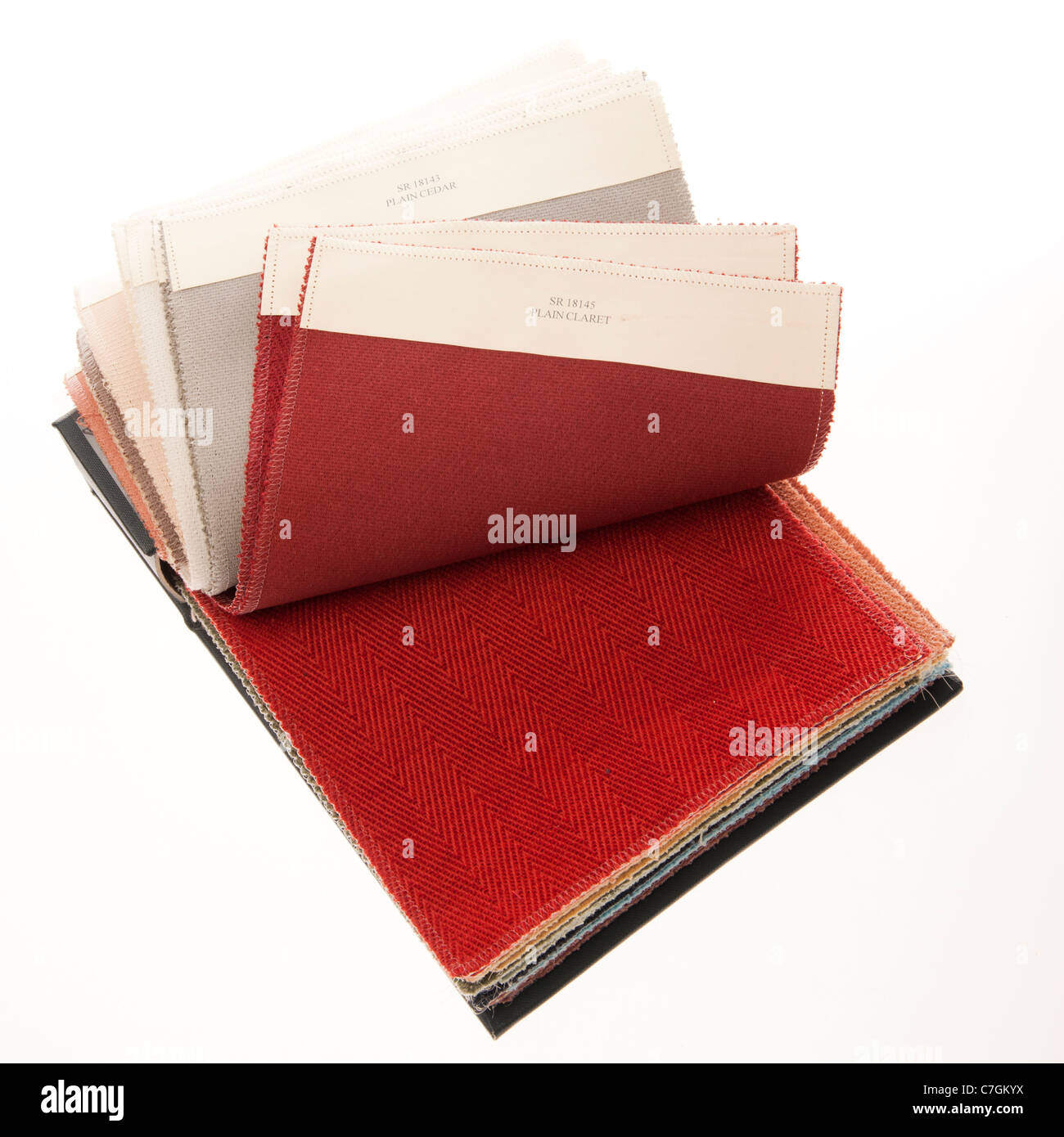 A sample swatch book of upholstery fabric fabrics textiles - Stock Image
